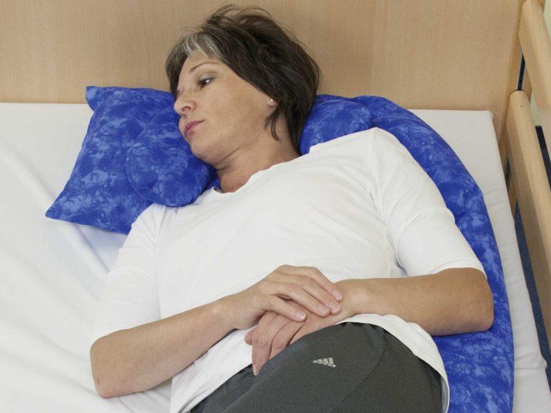 Frau positioniert auf Lagerungsschlange: Lagerungskissen wird am Rücken entlang an modelliert. Das Kissen stützt Kopf und Rumpf der Patientin. Oberkörper des Patienten in 30 ° Positionierung.