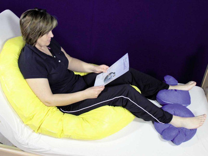 Positionierung einer Person in stabiler Sitzposition mit Lagerungsschlange und 2 Universalhörnchen für die Füße