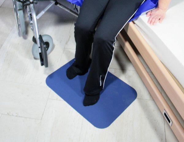 Person sitzt am Bettrand, die Füße sind auf einer Anti-Rutschmatte abgestellt