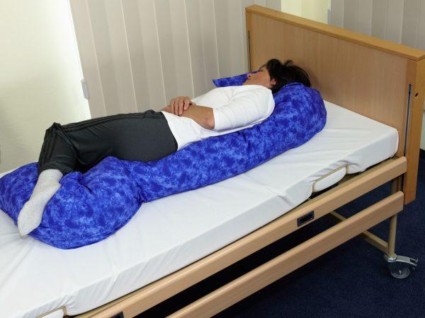 Frau in 30 ° Positionierung auf langer Lagerungsschlange in blau. Sie hat hier nur 1 Kissen vom Kopf bis zum Fuß. Die Beine sind bequem angewinkelt