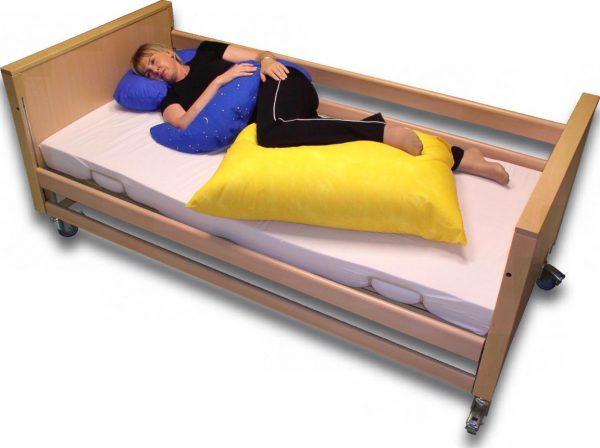 Bobath-Lagerung mit drei Kissen: Halbmondkissen, großes Beinkissen, kleines Entspannungskissen