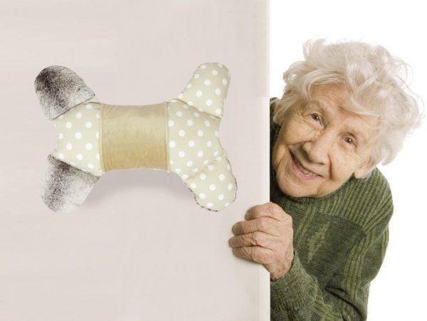 Alte Frau schaut freundlich lächelnd hinter einer Wand hervor. Auf der Wand ist ein Therapie-Fühlkissen für Menschen mit Demenz zu sehen. Das Kissen ist in Flügelform. Das Grundkissen ist beige mit weißen Punkten. Die 4 Schenkel sind abgesteppt. Die 2 gegenüberliegenden Schenkel haben graue Felleinstecktaschen. Am Korpus ist ein weicher beiger PE Muff zum Streicheln und zum Verstecken oder Wärmen der Hände.