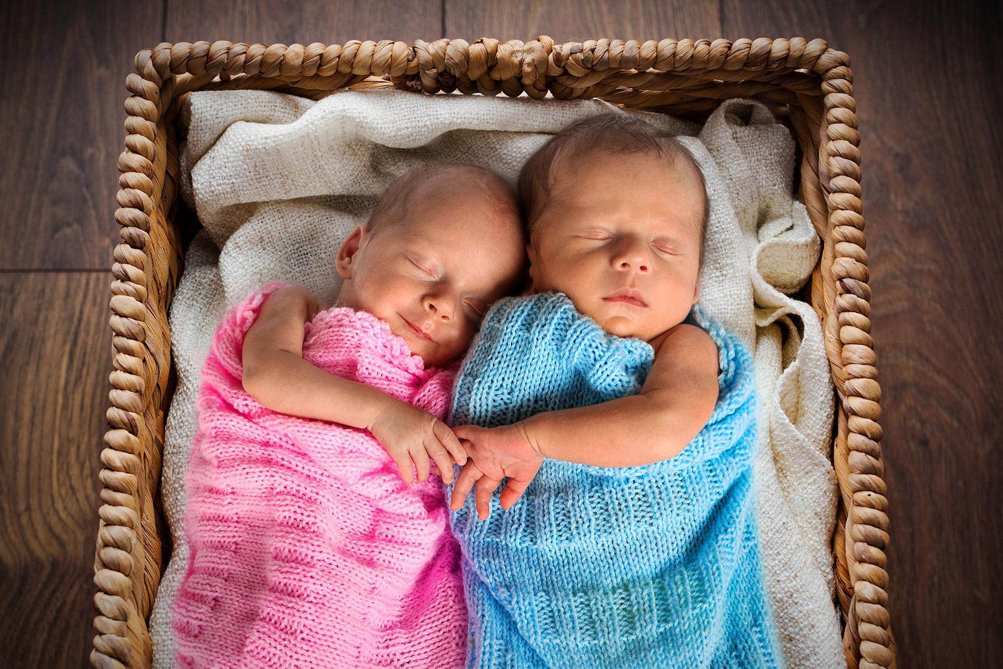 zwei Babys halten sich an den Händen während sie schlafen