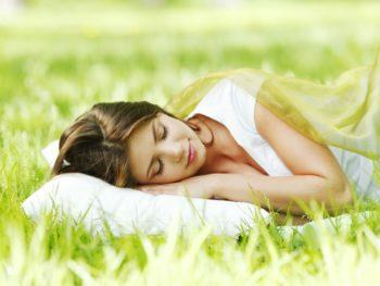 Junge Frau schläft auf einem Kopfkissen im Gras