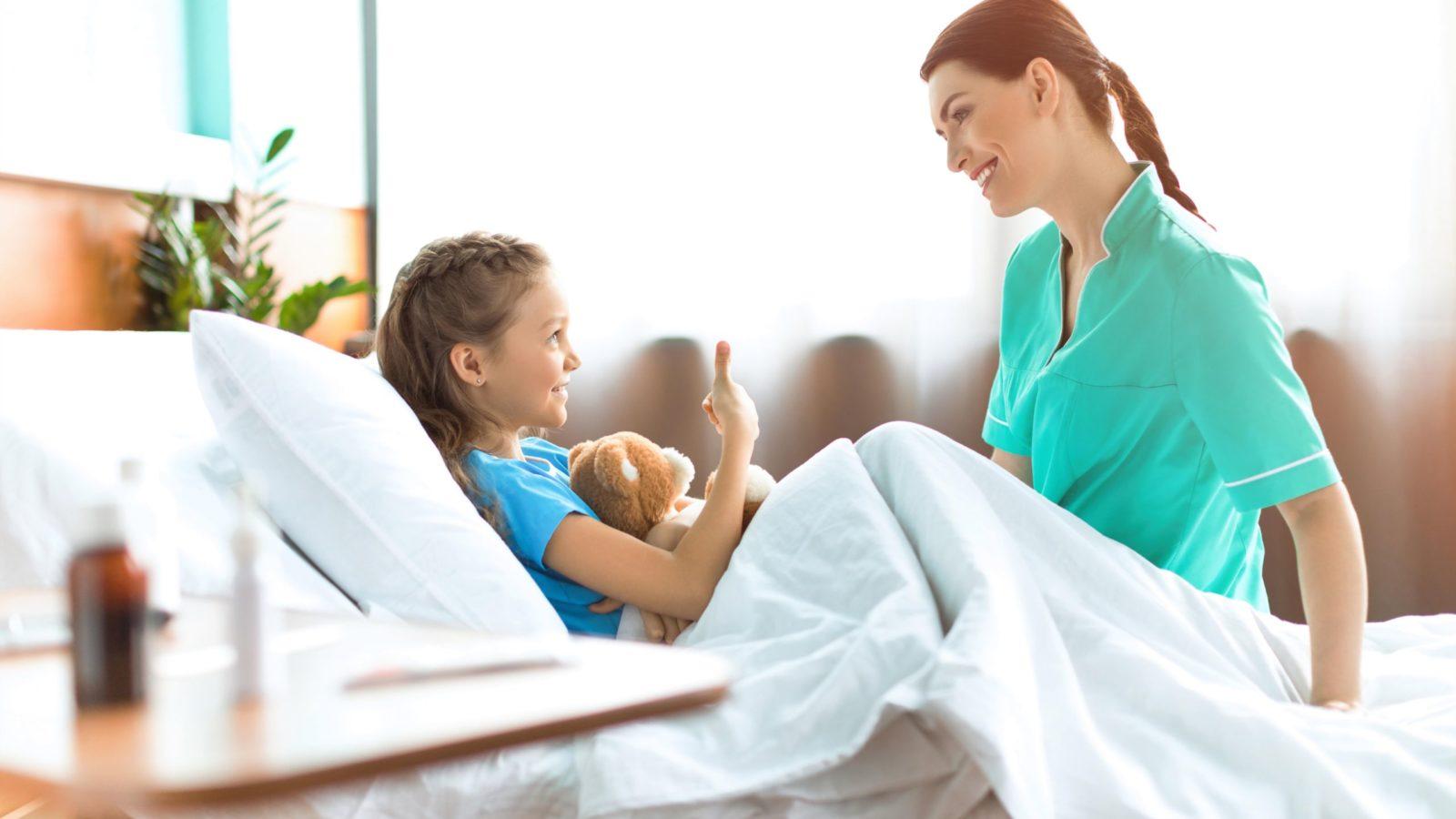 Kategoriebild Kinder - Mädchen im Krankenbett mit Krankenschwester, die auf dem Bett sitzt
